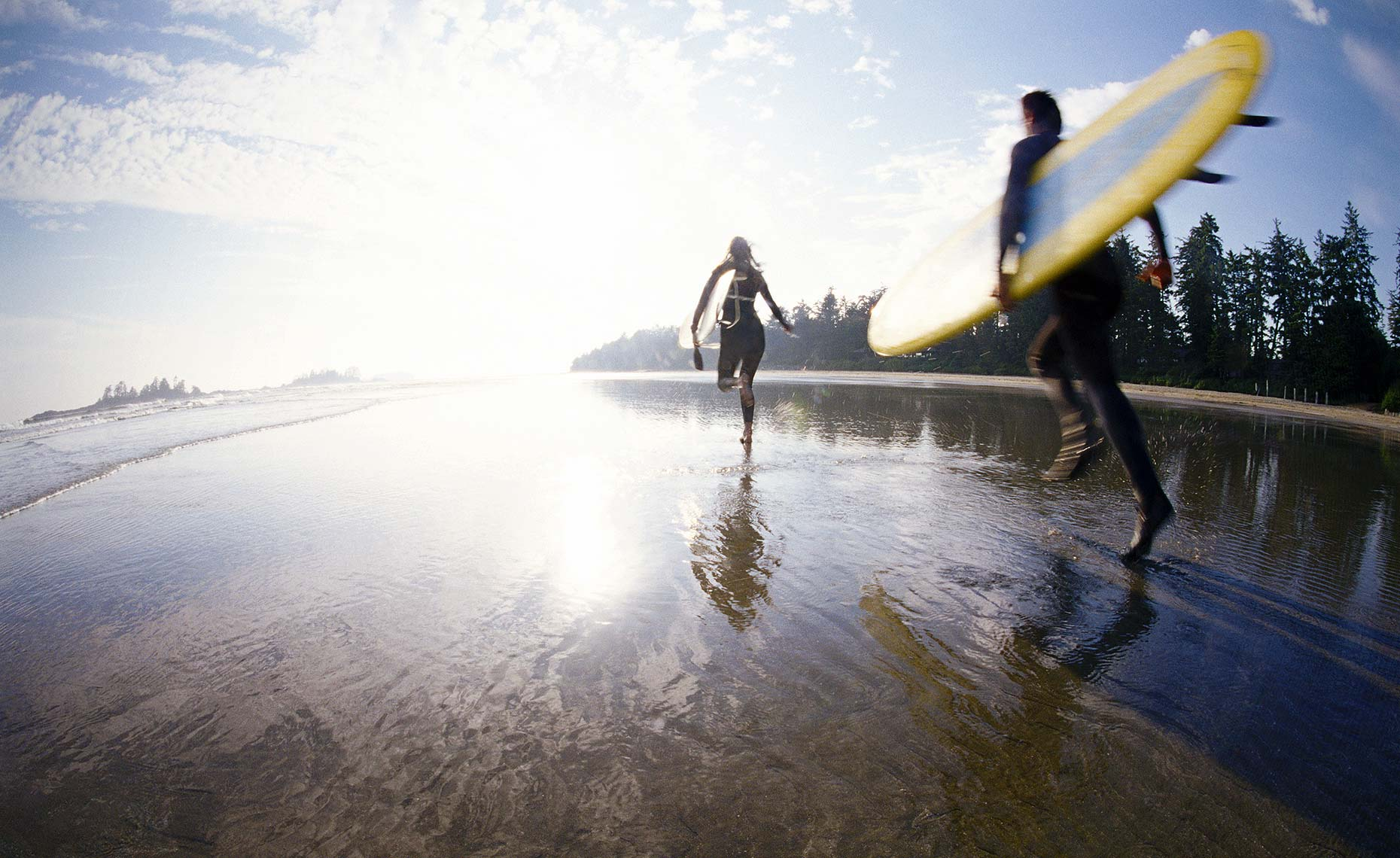 Tofino surfers running on beach